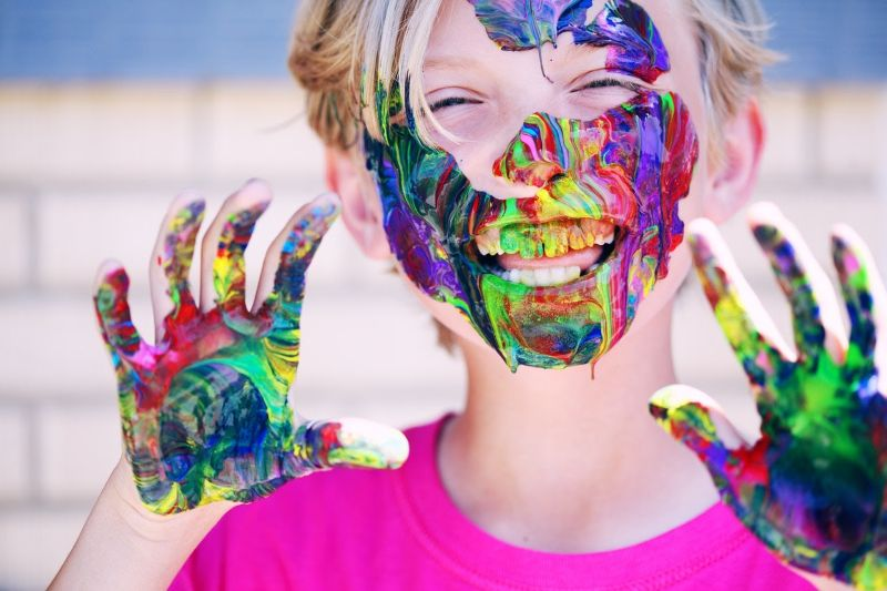 child with paint on his hands and face